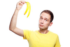 Unhappy boy with banana skin. Disappointed handsome guy holding banana skin over white background. Studio shot Stock Photography