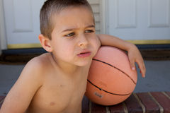 Unhappy Boy With Basketball. Cute little boy with an arm on his basketball Royalty Free Stock Photos