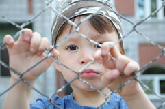 Unhappy boy behind bars Royalty Free Stock Photography