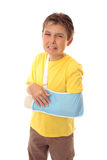 Unhappy boy broken arm. Injured young boy with sore arm iin an arm sling stock images