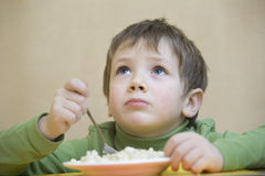 Unhappy Boy Eating Food While Looking Up Royalty Free Stock Photography