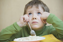 Unhappy Boy With Food Looking Up At Table Royalty Free Stock Photos