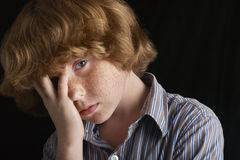 Unhappy Boy With Hand On Face. Closeup of unhappy young boy with hand on face over black background Stock Image