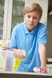 Unhappy Boy Helping to Clean House Stock Images