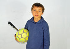 Unhappy Boy With A knife Stuck in his Football Royalty Free Stock Image