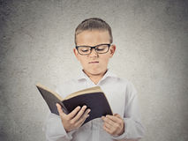 Unhappy Boy Reading Book. Closeup Portrait Unhappy Child, Boy holding Reading Book, displeased with story, information provided, isolated grey Wall Background royalty free stock photography
