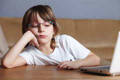 Unhappy boy sits in front of his laptop Royalty Free Stock Photos