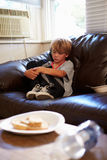 Unhappy Boy Sitting On Sofa At Home Stock Image