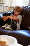 Unhappy Boy Sitting On Sofa At Home Royalty Free Stock Images