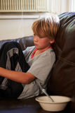 Unhappy Boy Sitting On Sofa At Home Stock Photos
