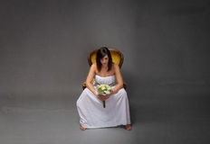 Unhappy bride sitting with bouquet on hand stock images