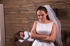 Unhappy bride, sleeping groom on background Stock Photos