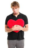 Unhappy broken heart valentines day man. Unhappy love. Funny image of sad broken heart valentines day man holding red heart isolated on white background Royalty Free Stock Photo