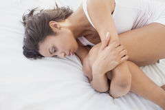 Unhappy brunette lying on bed holding her knees Royalty Free Stock Photo