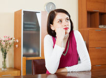 Unhappy brunette woman at table Royalty Free Stock Image