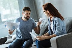 Unhappy brutal man being angry at his girlfriend. You did it. Unhappy brutal brunette men holding documents and looking at his girlfriend while being angry at Royalty Free Stock Photos