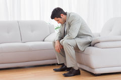 Unhappy buinessman sitting on sofa lowering his head Royalty Free Stock Image