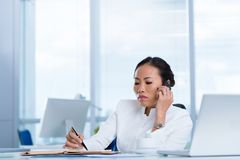 Unhappy business lady. Making notes while talking on the phone Royalty Free Stock Image