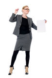 Unhappy business woman with a blank sheet of paper. Girl in full growth Royalty Free Stock Images