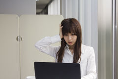 Unhappy business woman in front of Laptop computer in office Royalty Free Stock Images
