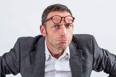 Unhappy businessman with eyeglasses on his forehead for suspicion Stock Images
