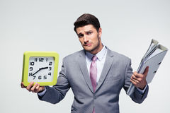 Unhappy businessman holding folders and clock Stock Image