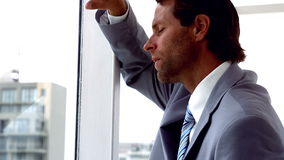 Unhappy businessman looking out window stock video footage