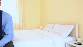 Unhappy businessman sat on bed stock footage