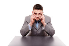 Unhappy businessman sitting at desk with hands on forehead Stock Photography