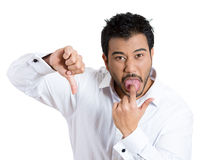 Unhappy businessman sticking tongue out in disgust, and showing thumbs down Royalty Free Stock Image