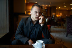 Unhappy businessman talking on phone in restaurant Stock Images