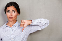 Unhappy businesswoman with thumb down looking away Royalty Free Stock Image