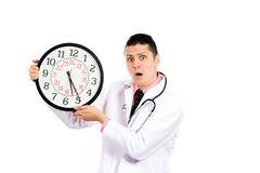 Unhappy busy scheduled male health professional holding a big clock Royalty Free Stock Images