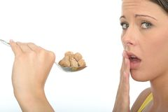 Unhappy Cautious Young Woman Holding a Spoonful of Brown Sugar Cubes Royalty Free Stock Photo