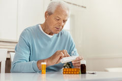 Unhappy cheerless man taking medicine. Being ill. Unhappy cheerless senior man holding a box with pills and taking medicine while being ill Stock Images