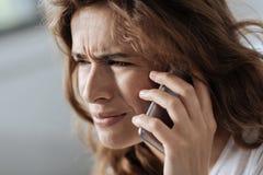 Unhappy cheerless woman listening to her interlocutor Stock Image