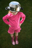 Unhappy child. Young girl with a saucepan on her head Stock Photography