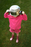 Unhappy child. Young girl with a saucepan on her head Stock Photo