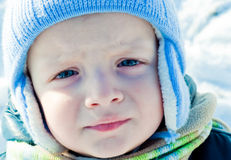 Unhappy child. Portrait of a child with blue eyes upset in a winter setting Royalty Free Stock Image