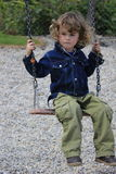 Unhappy child. Little boy with a sad expression sitting on a swing Royalty Free Stock Images