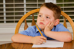 Unhappy child doing his homework. At kitchen table at home royalty free stock photos
