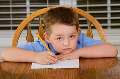 Unhappy child doing his homework. At kitchen table at home royalty free stock images