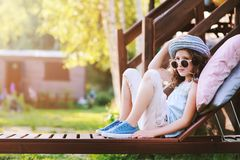 Unhappy child girl relaxing on sunbed in summer garden. On vacation Stock Photos