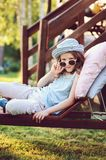 Unhappy child girl relaxing on sunbed in summer garden. On vacation Royalty Free Stock Photos