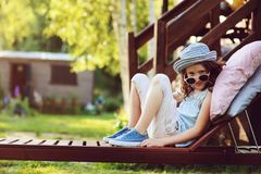 Unhappy child girl relaxing on sunbed in summer garden. On vacation Stock Images