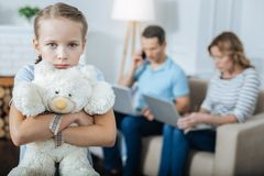Unhappy child and her parents working. Childhood. Lonely blue-eyed fair-haired little girl standing and holding her toy and her parents working in the background Stock Photo