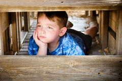 Unhappy child hiding and sulking. While playing on playground Royalty Free Stock Photos