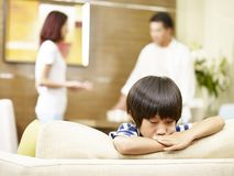Unhappy child and quarreling parents. Asian child appears sad and unhappy while parents quarreling in the background Stock Image