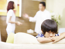 Unhappy child and quarreling parents. Asian child appears sad and unhappy while parents quarreling in the background Royalty Free Stock Images