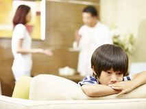 Unhappy child and quarreling parents. Asian child appears sad and unhappy while parents quarreling in the background royalty free stock photo